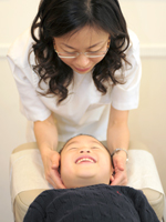 Dr. Ng performs chiropractic adjustment on kids